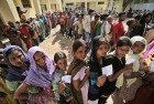 People stand in a queue outside a polling station to cast their votes for Lok Sabha elections in Jammu.