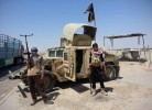Al-Qaeda inspired militants stand with captured Iraqi Army Humvee at a checkpoint outside Beiji refinery, some 250 kilometers (155 miles) north of Baghdad, Iraq.