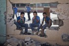 Children sit on a damaged wall of a school in Gaza City's Shijaiyah neighborhood.
