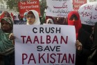 Supporters of Pakistan Awami Tehreek hold up posters to condemn the Taliban attack in Peshawar.