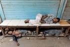 Streetkids sleep on a bench on a roadside pavement in Old Delhi