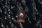 An Iranian woman holds up a poster showing Sheikh Nimr al-Nimr, a prominent opposition Saudi Shiite cleric who was executed last week by Saudi Arabia, in Tehran, Iran.