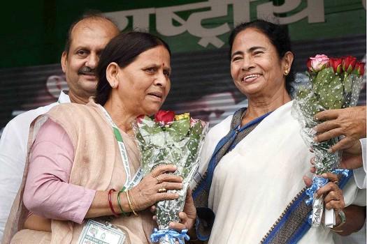 RJD senior leader Rabri Devi greets West Bengal Chief Minister Mamata Banerjee during the 'BJP bhagao, desh bachao' rally at Gandhi Maidan in Patna.
