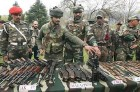 Army personnel displaying the arms and ammunition seized from the militants after the five-day long encounter in Kupwara district
