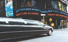 A Limo rolls past Times Square on Sept 15, as dire financial news is displayed on a ticker