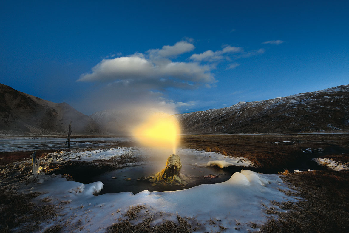 The glow of a headlamp transforms erupting steam and water into a halo around the head of a geyser. Even at a temperature of -25 degrees, the water is a scalding 80 degrees celcius, the boiling point at 4,000m above sea level