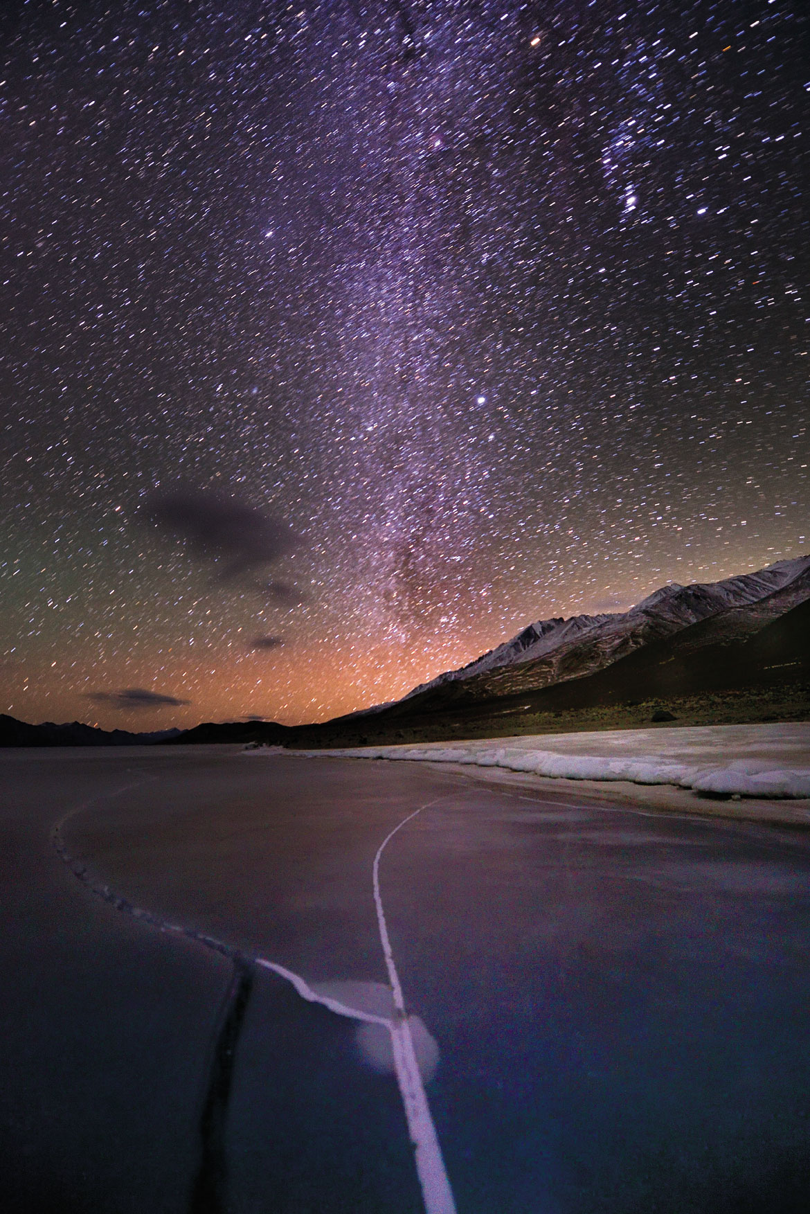 A crack on the frozen Pangong Tso reflects the Milky Way that arches over it. Cloudless new moon nights on the Changthang are often bright enough for stars to paint the lake ice