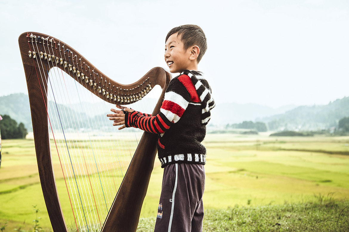 A young boy plays a harp at the Ziro Festival of Music, Arunachal Pradesh