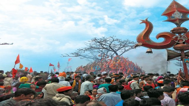 Pilgrims paying obeisance to the stacked trishuls atop Chauragarh mountain