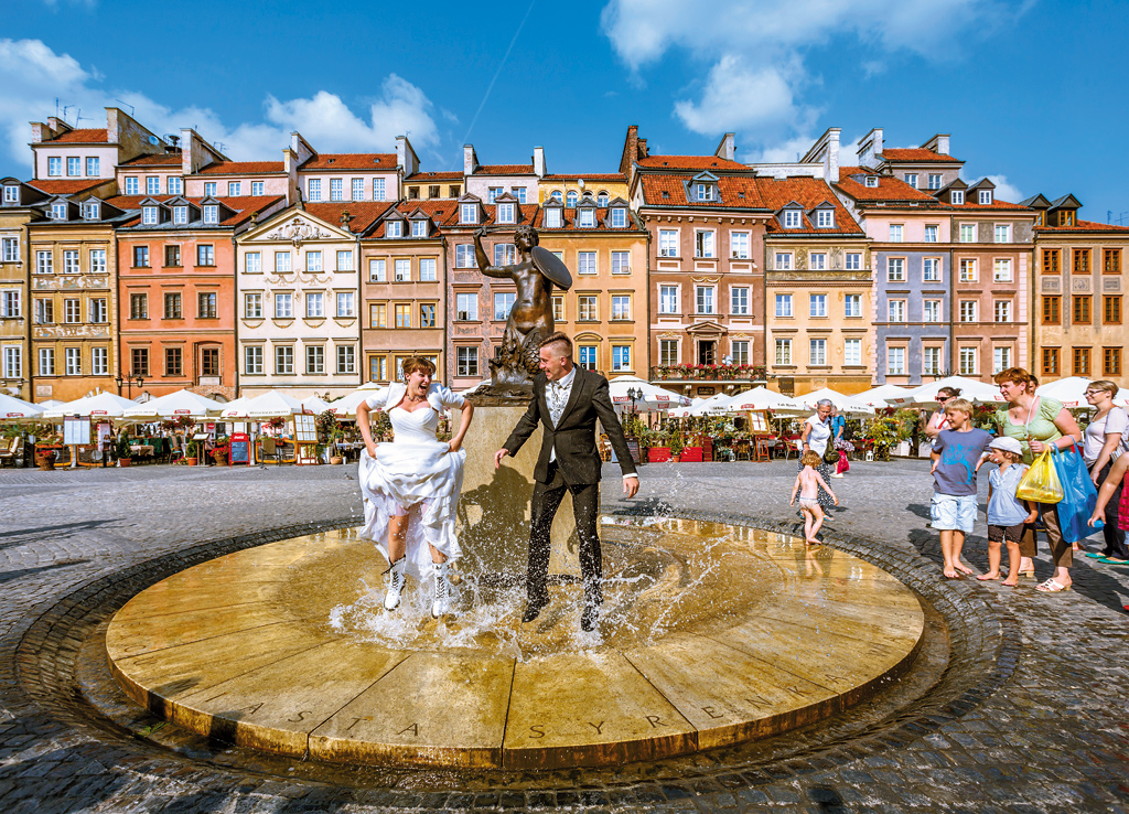 Newly-weds splash around the Mermaid Statue, Warsaw Old Town, Poland. WWII saw 85 per cent of the historic centre destroyed, but over five years the old town was completely rebuilt—a feat that catapulted it into the UNESCO list.