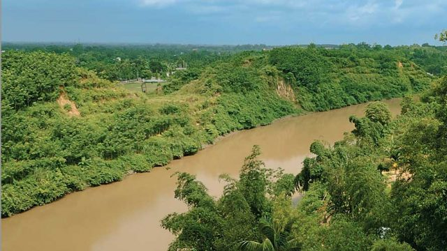 The muddy Gomati river flowing past a lush landscape