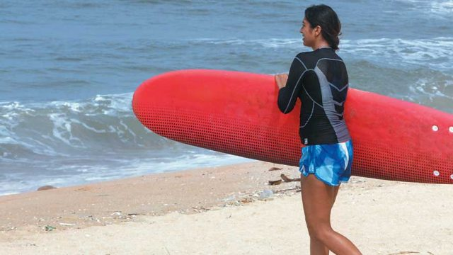 A surfer heads towards the sea with her board in hand