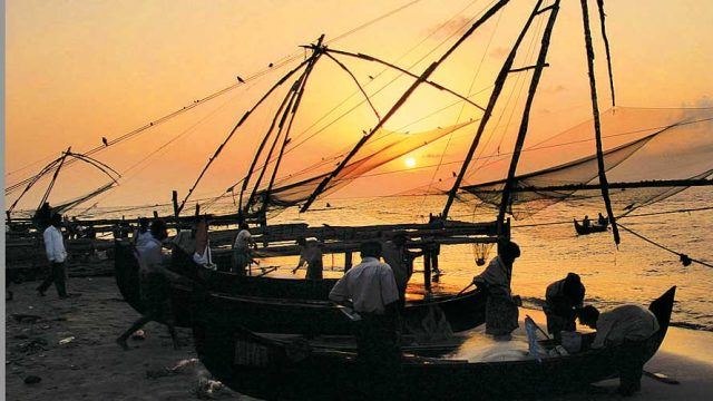 Fishermen hauling in their large Chinese fishing nets at Kochi