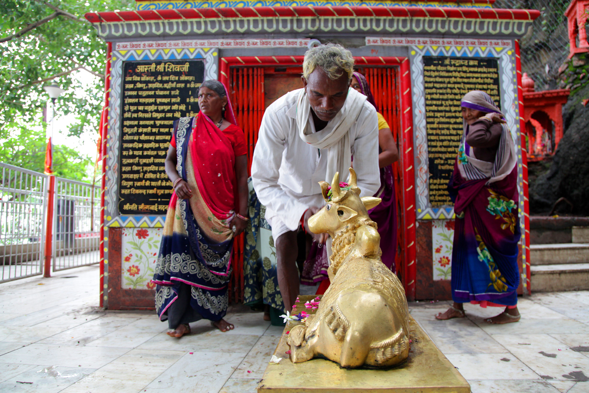 Pilgrims offer their respect to Nandi at a small Shiva shrine near Ma Chamunda temple in Dewas