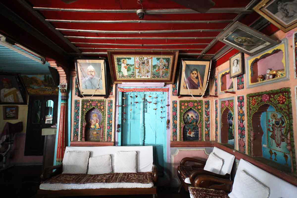 Paintings of gods and goddesses adorn the niches and walls, with photos of some of the Hathiwala ancestors hanging alongside