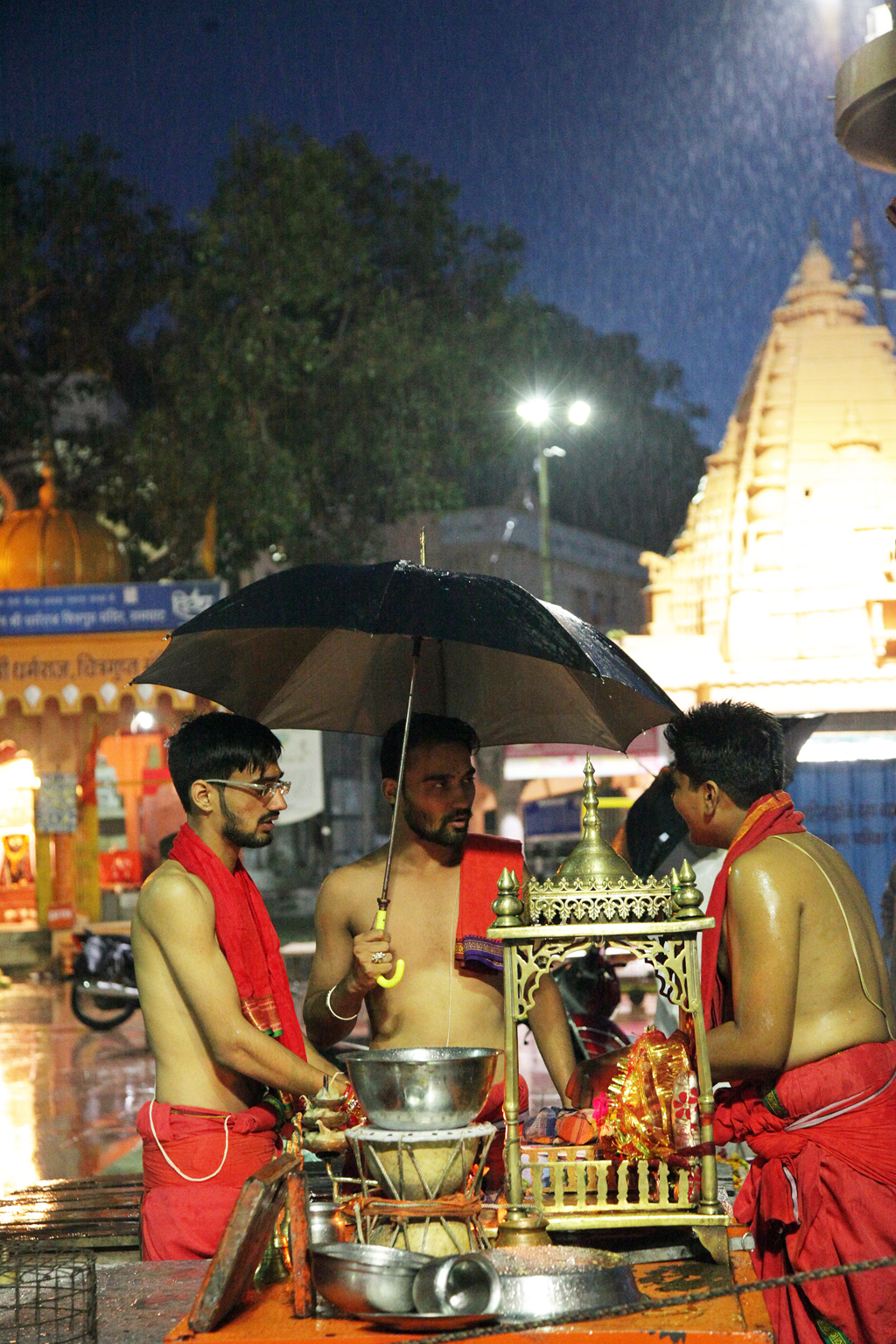 Priests discuss where to shift the puja after a sudden squall disrupts the traditional evening ritual.