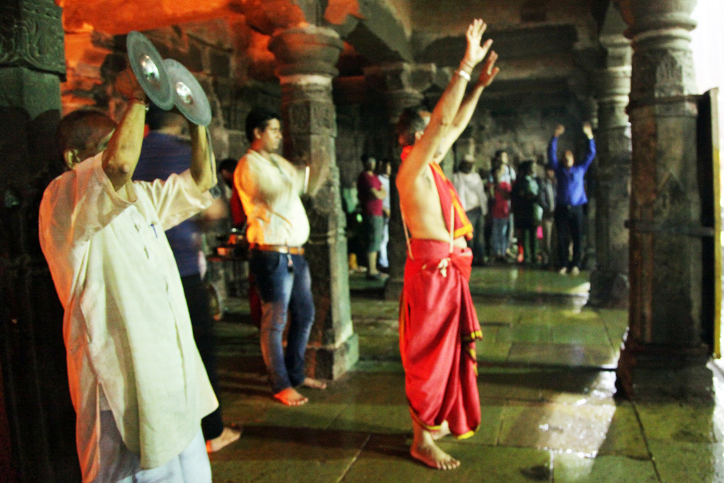 Priests and devotees alike raise their hands, hailing the sacred river.