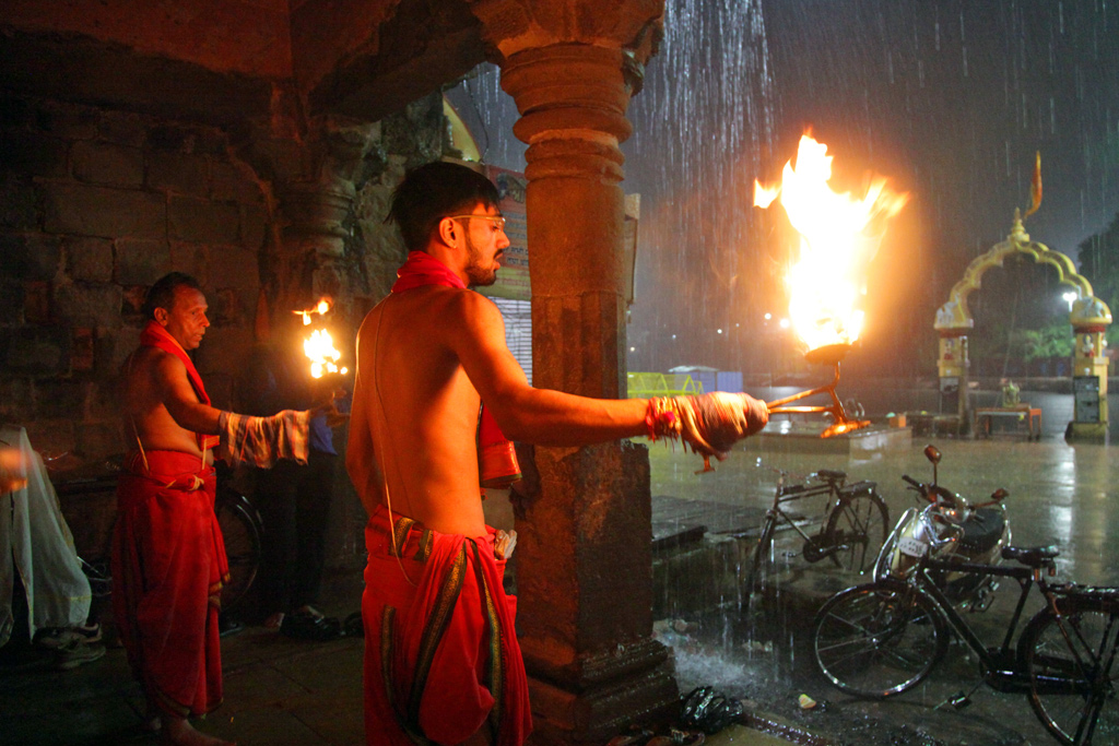 A row of priests swing flaming oil lamps in synchrony in reverence to the river.