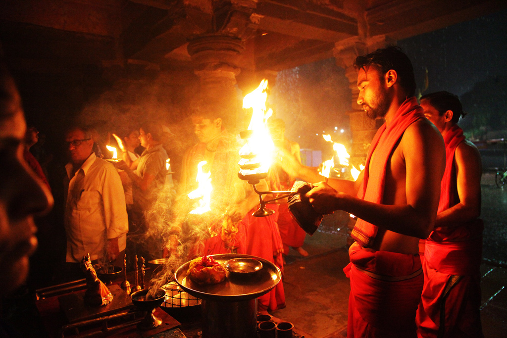 A priest waves the sacred fire from the lamp as an offering to the river deity.