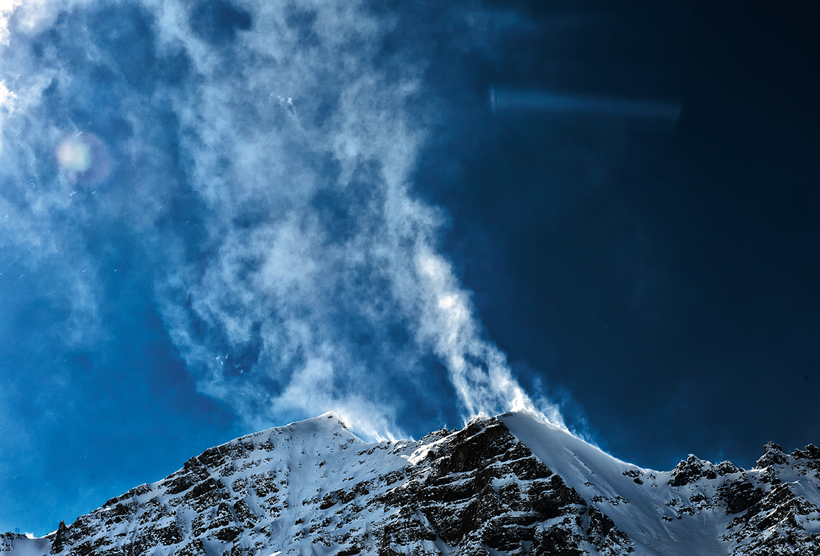 High winds create magnificent snow plumes atop the summit of Stok Kangri.