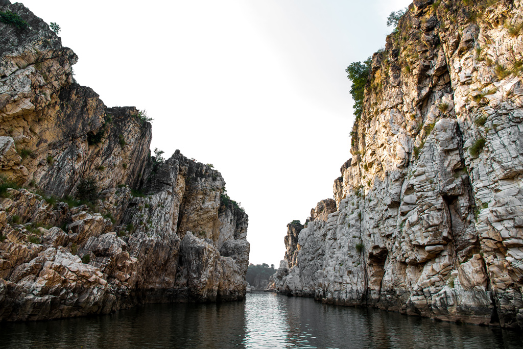Marble Rock's craggy rock faces are reflected in the calm waters of the Narmada.