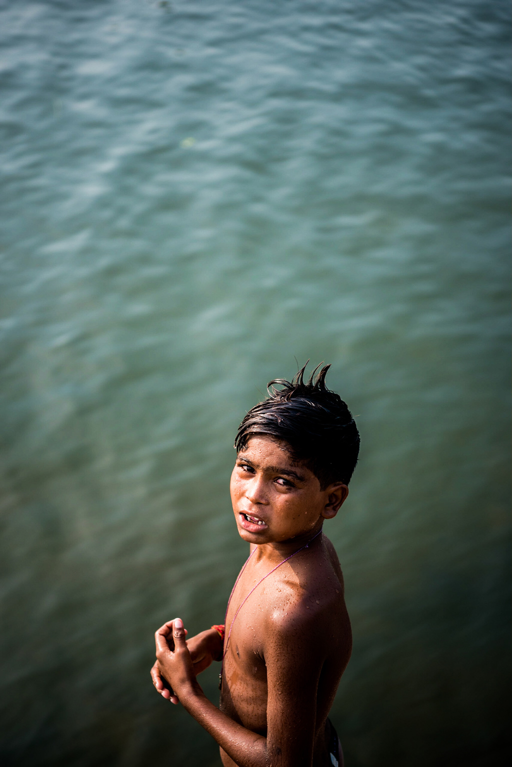 A local boy makes some pocket money by asking visitors to throw a coin into the water, which he dives in and fishes out.