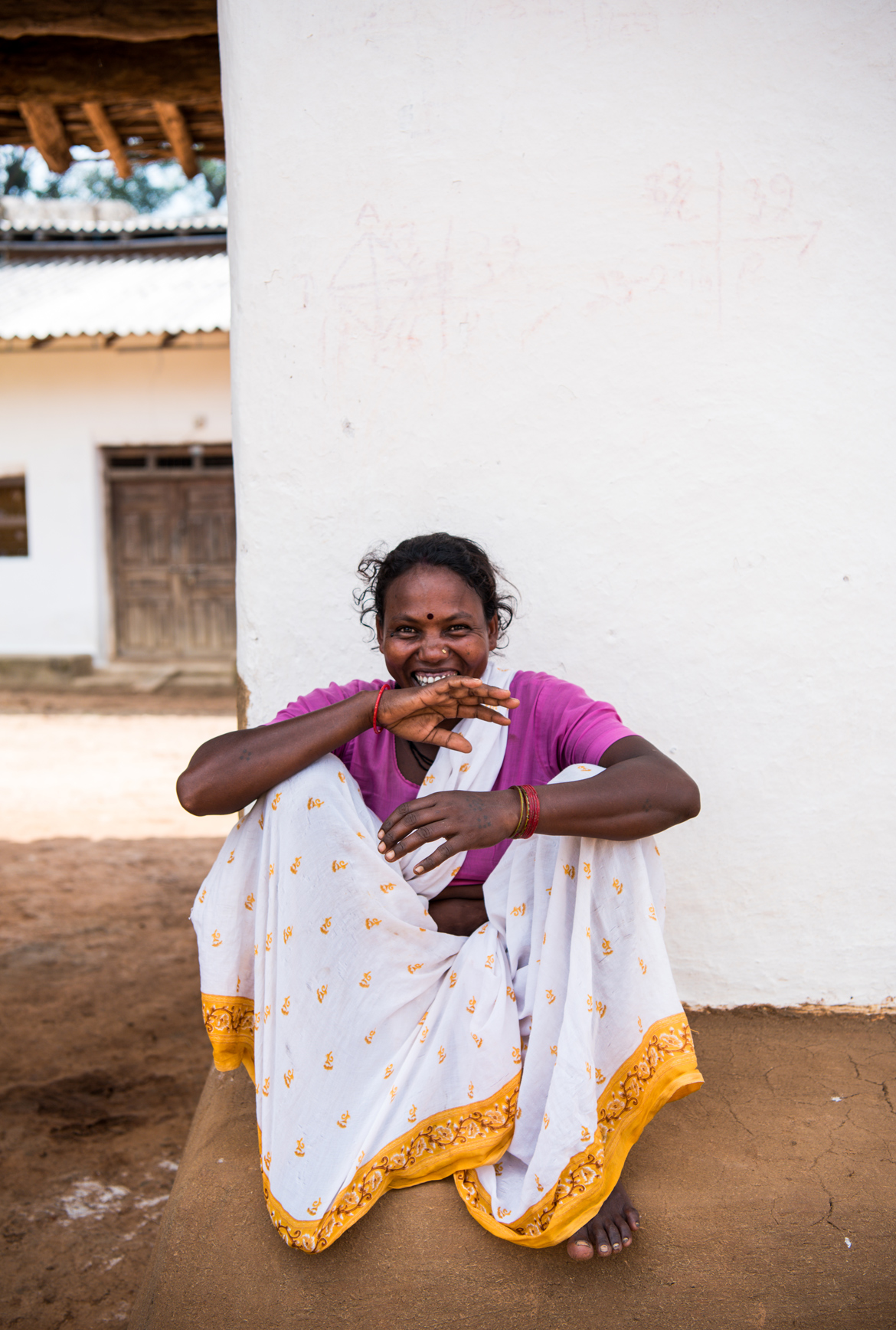 A Gond woman sits outside her mud home.