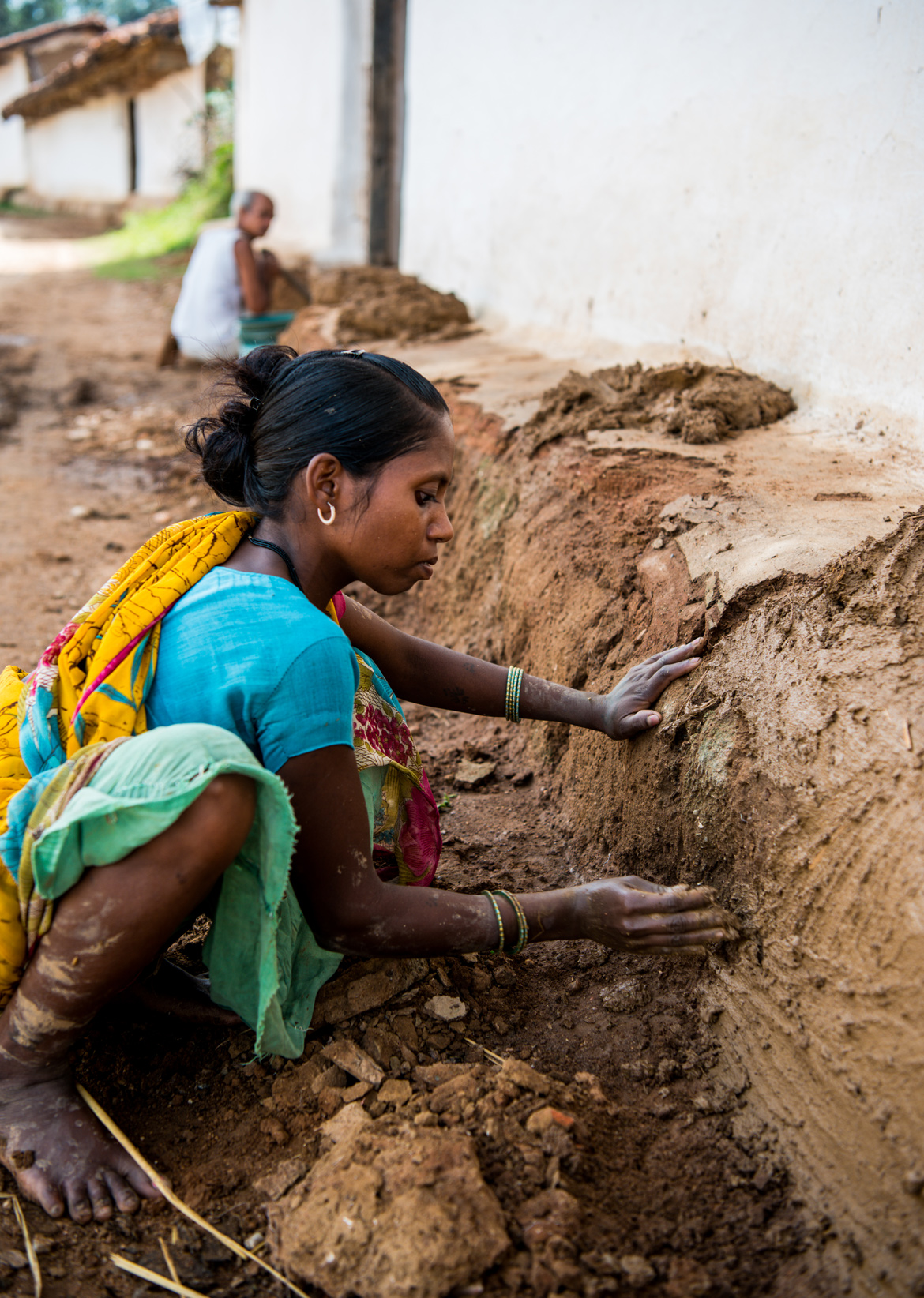 A woman reinforces mud onto the otla, or platform around her village home.