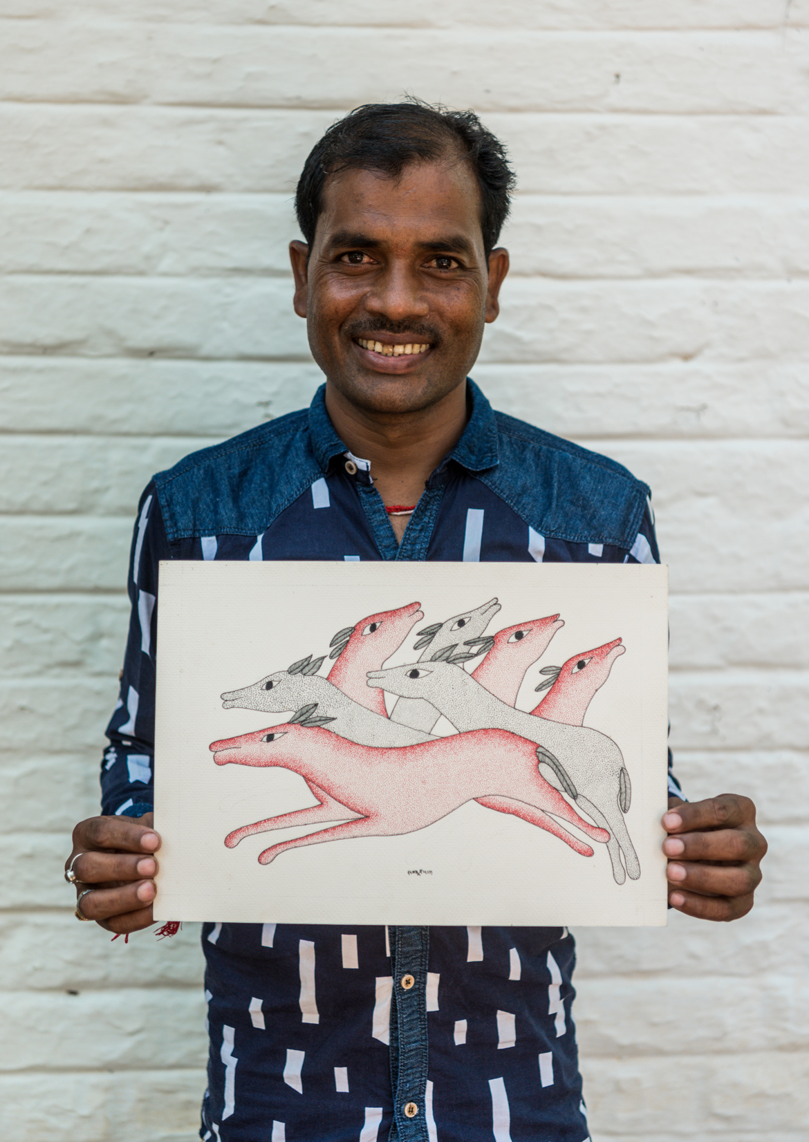 Ram Kumar Shyam, an artist from Patangarh village poses with one of his artworks at Kipling Camp in Kanha