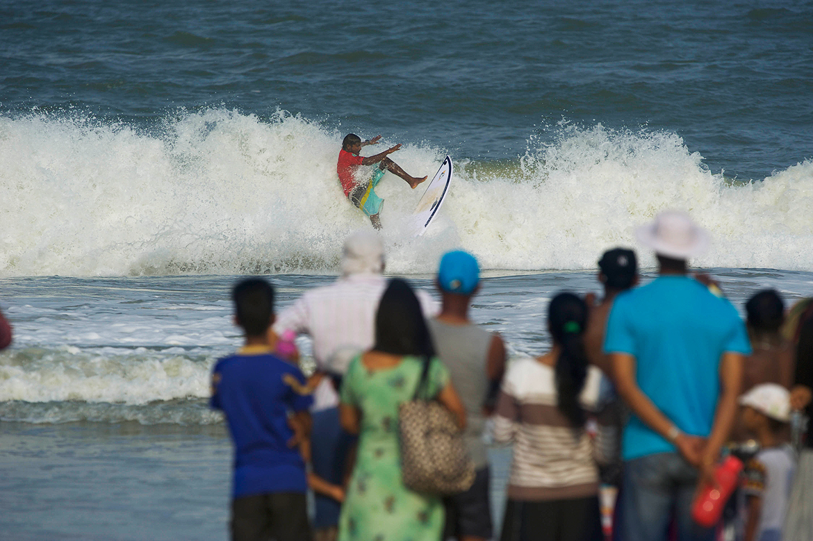 The crowd stares affixed at a surfer performing maneouvers