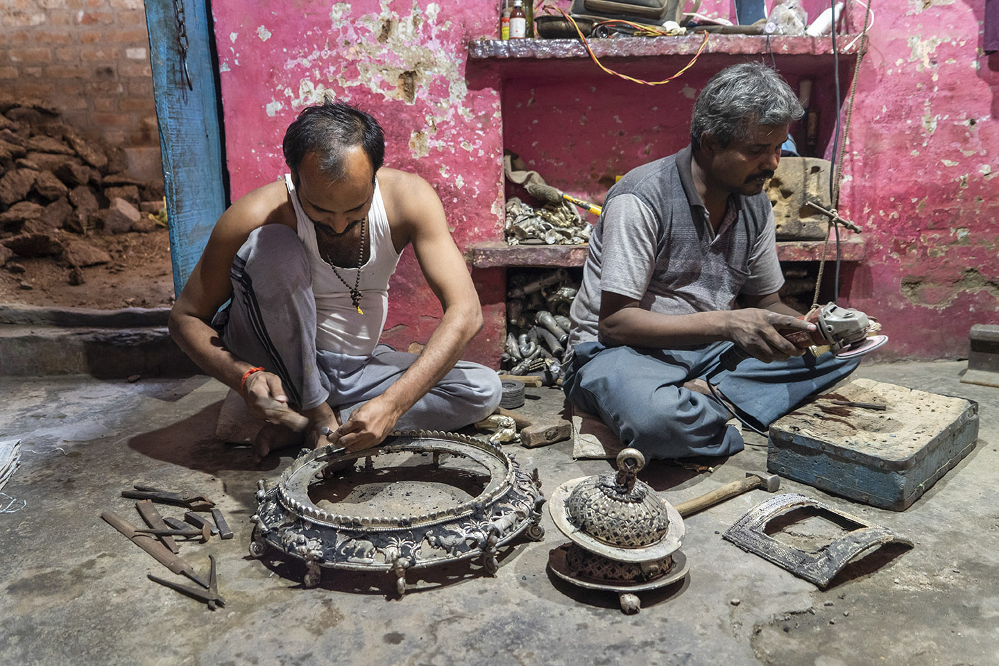 Om Prakash (right) and Laxmi Narayan (left) working on a bell metal birdcage in their home